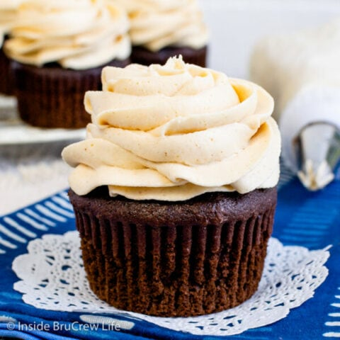 A chocolate cupcake on a blue towel with a honey peanut butter frosting swirl on top.
