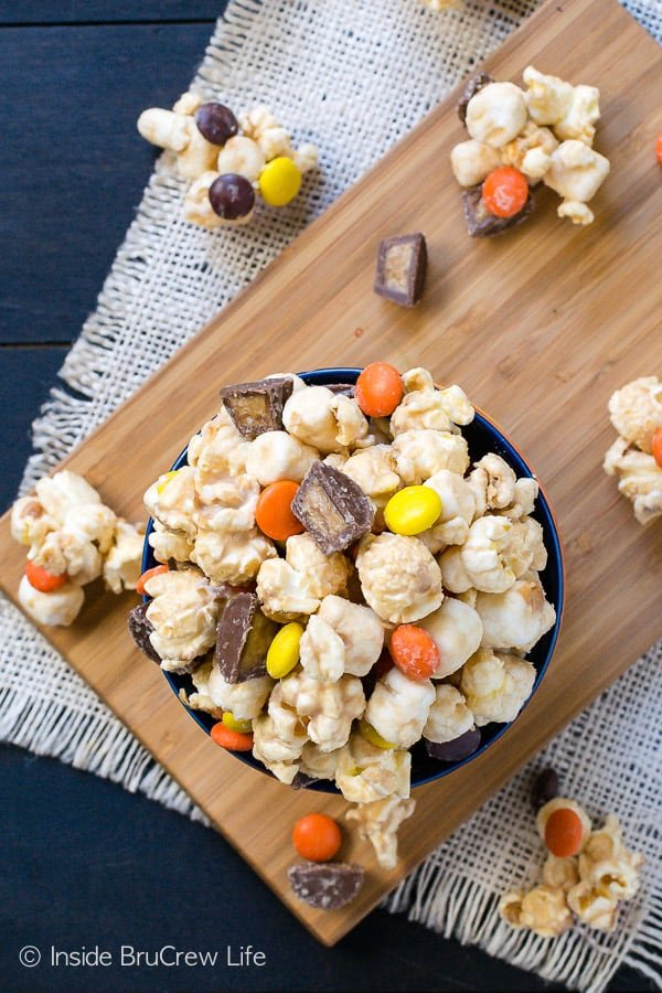 Salted Caramel Reese's Popcorn - this sweet and salty no bake snack mix is loaded with Reese's candies and sea salt. Try this easy recipe for your next movie night! #popcorn #saltedcaramel #peanutbuttercups #reesespieces #snackmix #nobake #sweetandsalty