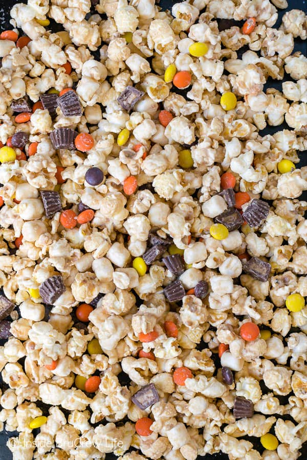 Salted Caramel Reese's Popcorn - this caramel coated snack mix is loaded with peanut butter cups, Reese's pieces, and sea salt. Make this recipe for your next movie night! #popcorn #saltedcaramel #peanutbuttercups #reesespieces #snackmix #nobake #sweetandsalty