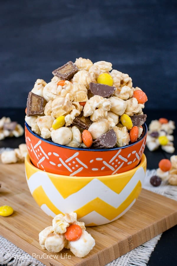Salted Caramel Reese's Popcorn - this easy snack mix is loaded with salted caramel and two kinds of Reese's candies. Make this recipe to munch on during movie nights! #popcorn #saltedcaramel #peanutbuttercups #reesespieces #snackmix #nobake #sweetandsalty
