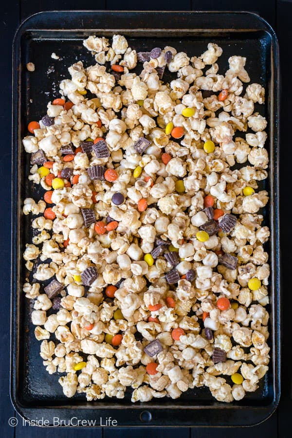 Salted Caramel Reese's Popcorn - two kinds of Reese's candies and sea salt give this caramel popcorn a sweet and salty flair. Try this snack mix recipe for your next movie night! #popcorn #saltedcaramel #peanutbuttercups #reesespieces #snackmix #nobake #sweetandsalty