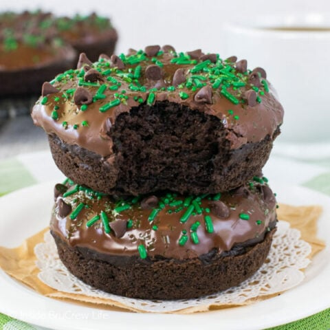 Two baked chocolate zucchini donuts stacked on a white plate.