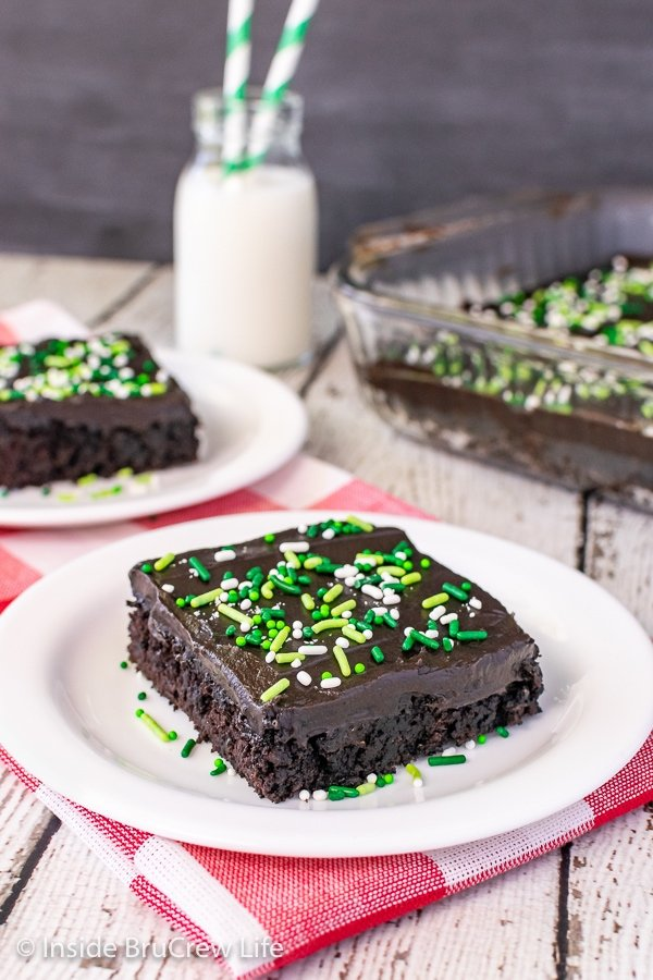 Two white plates with pieces of chocolate zucchini cake with frosting on them