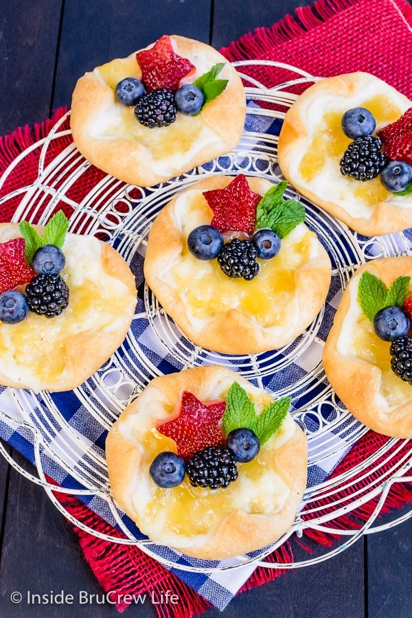 Overhead picture of a white wire rack with lemon cheese danishes with lemon curd and fruit on it.