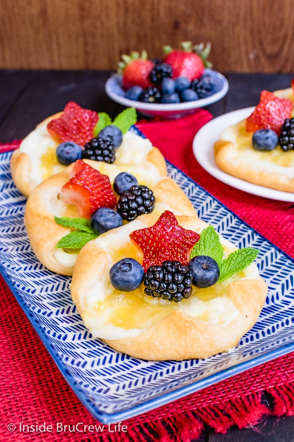 A blue and white plate with three cream cheese danishes topped with lemon curd and fresh fruit on it.