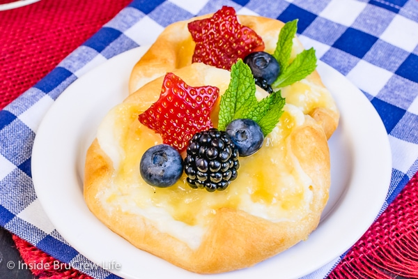 Two lemon cheese danishes topped with fresh berries and mint leaves on a white plate.