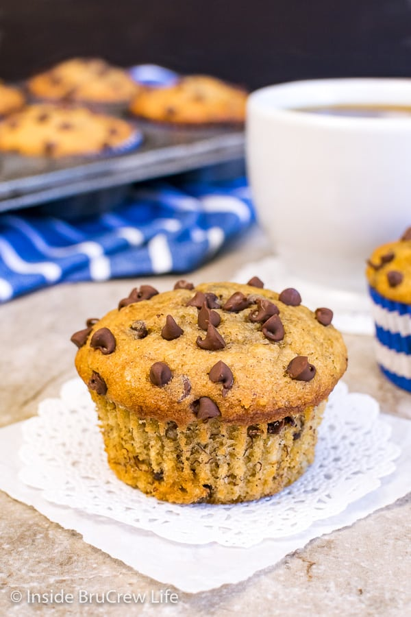 A white doily with a peanut butter chocolate chip banana muffin on it and a muffin tin behind it
