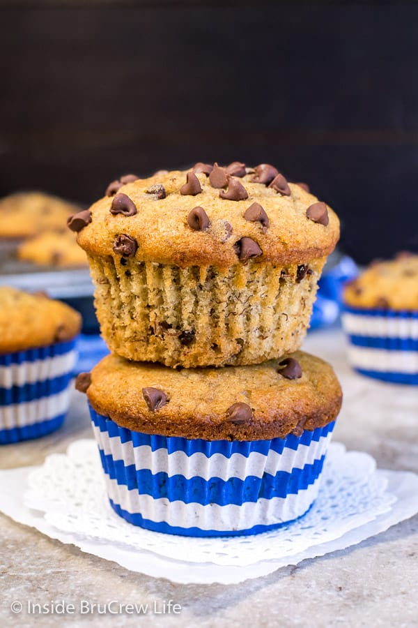 Two peanut butter chocolate chip banana muffins stacked on top of each other on a white doily