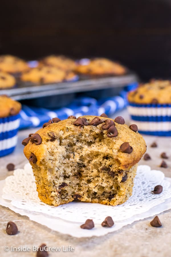 A close up picture of peanut butter chocolate chip banana muffin on a white doily with a bite taken out of it