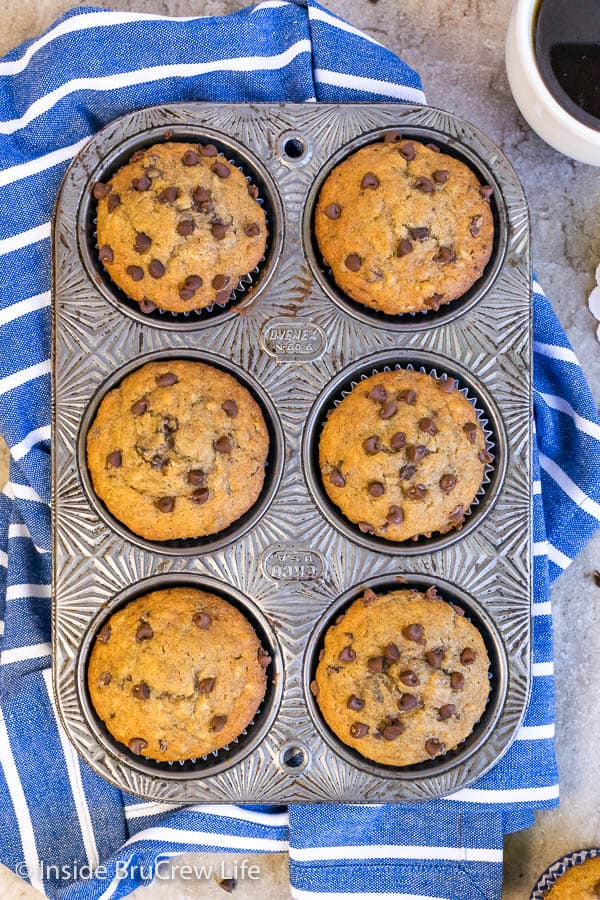 Overhead picture of 6 peanut butter chocolate chip banana muffins in a muffin tin on a blue towel