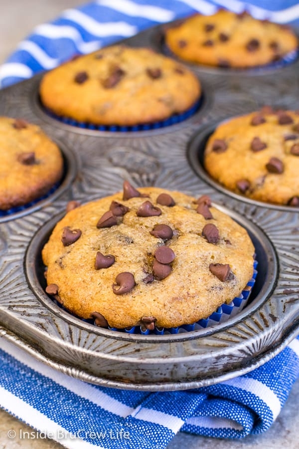A close up picture of a peanut butter chocolate chip banana muffin in a silver muffin tin