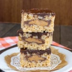 A white plate with three peanut butter rice krispies stuffed with peanut butter cups stacked on it