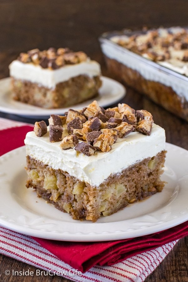 A close up picture of a piece of apple Snickers cake topped with chopped up Snickers candy bars