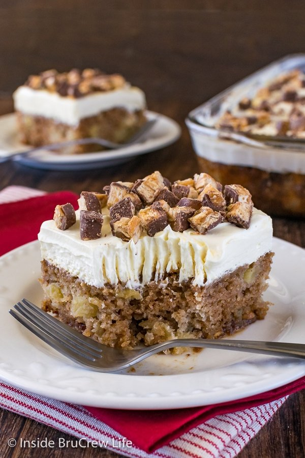 A piece of apple Snickers cake with fluffy frosting on a white plate with a bite take out of it