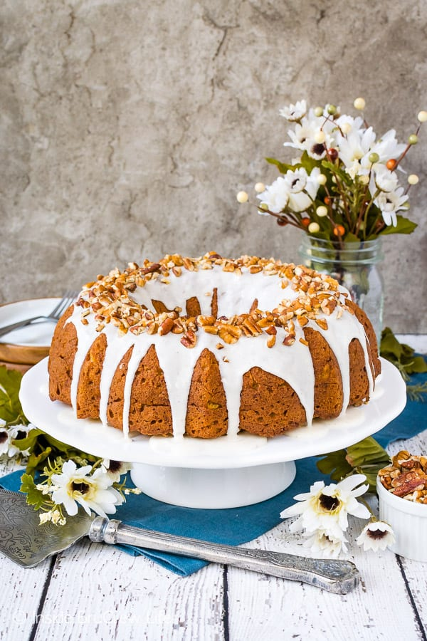 Chai Spiced Apple Bundt Cake - this soft homemade apple cake has chai spices and a sweet glaze with pecans on top. Try this fun and easy recipe for fall parties! #cake #apple #chai #bundtcake #homemade #crunchpak #fall #recipe