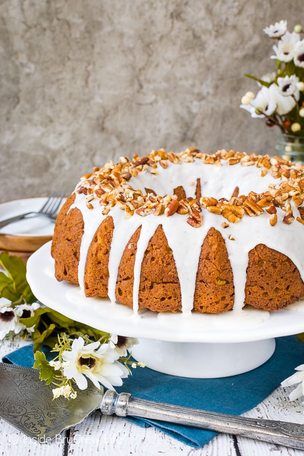 Chai Spiced Apple Bundt Cake - a sweet glaze and pecans make this homemade apple cake taste amazing! This cake will make your kitchen smell so good while it is baking! Great recipe for fall parties! #cake #apple #chai #bundtcake #homemade #crunchpak #fall #recipe