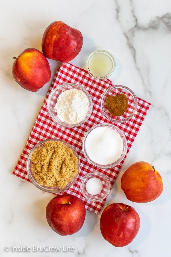 A white board with a red checkered towel and the ingredients to make a homemade apple pie filling recipe on it