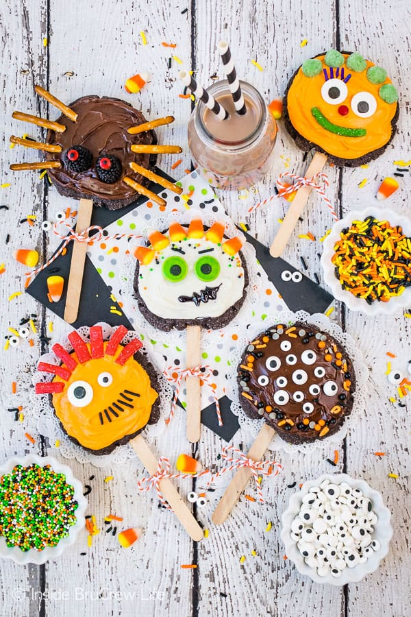 Make Your Own Monster Cookie Pops - adding a popsicle stick, frosting, and candies turns these easy sugar cookies into a fun monster cookie pop. Great recipe for kids to decorate at Halloween parties! #sugarcookies #chocolate #frosting #halloween #milklife #ad #pourmoremilk #halloweencrafts #halloweentreats #halloweenparty #simpleingredients #cookiepops #partyideas