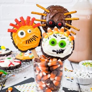 Make Your Own Monster Cookie Pops - decorating chocolate sugar cookies with frosting, sprinkles, and candy to make fun monster cookie pops. Great recipe to have kids make at Halloween parties. #sugarcookies #chocolate #frosting #halloween #milklife #ad #pourmoremilk #halloweencrafts #halloweentreats #halloweenparty #simpleingredients #cookiepops #partyideas