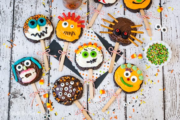 Make Your Own Monster Cookie Pops - turn sugar cookies into a fun monster cookie pops with frosting, candies, and sprinkles. Great recipe for kids to decorate at Halloween parties! #sugarcookies #chocolate #frosting #halloween #milklife #ad #pourmoremilk #halloweencrafts #halloweentreats #halloweenparty #simpleingredients #cookiepops #partyideas