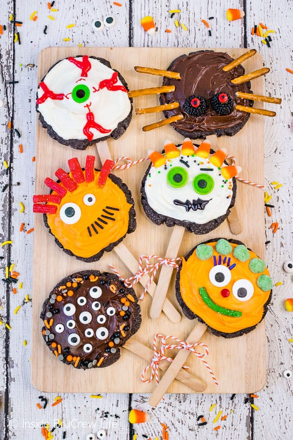 Make Your Own Monster Cookie Pops - these easy sugar cookie pops are transformed into a fun monster cookie with frosting, candies, and sprinkles. Great recipe for kids to decorate at Halloween parties! #sugarcookies #chocolate #frosting #halloween #milklife #ad #pourmoremilk #halloweencrafts #halloweentreats #halloweenparty #simpleingredients #cookiepops #partyideas