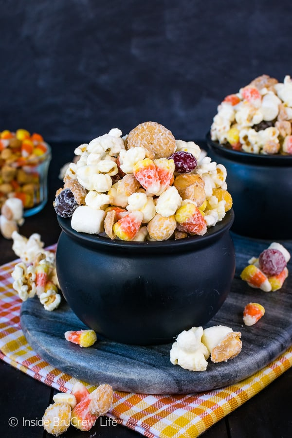 Candy Corn Popcorn Mix - white chocolate covered popcorn tossed with cookies, candy, and peanuts makes an irresistible snack mix. This no bake recipe is perfect for fall or Halloween parties! #snackmix #popcorn #whitechocolate #candycorn #peanuts #nutterbutters #fall #halloween #partymix