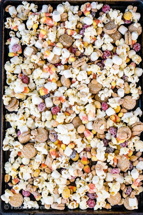 Candy Corn Popcorn Mix - popcorn loaded with cookies, candy, and marshmallows and coated in white chocolate makes an awesome snack mix. Make this easy no bake recipe for parties or movie nights! #snackmix #popcorn #whitechocolate #candycorn #peanuts #nutterbutters #fall #halloween #partymix