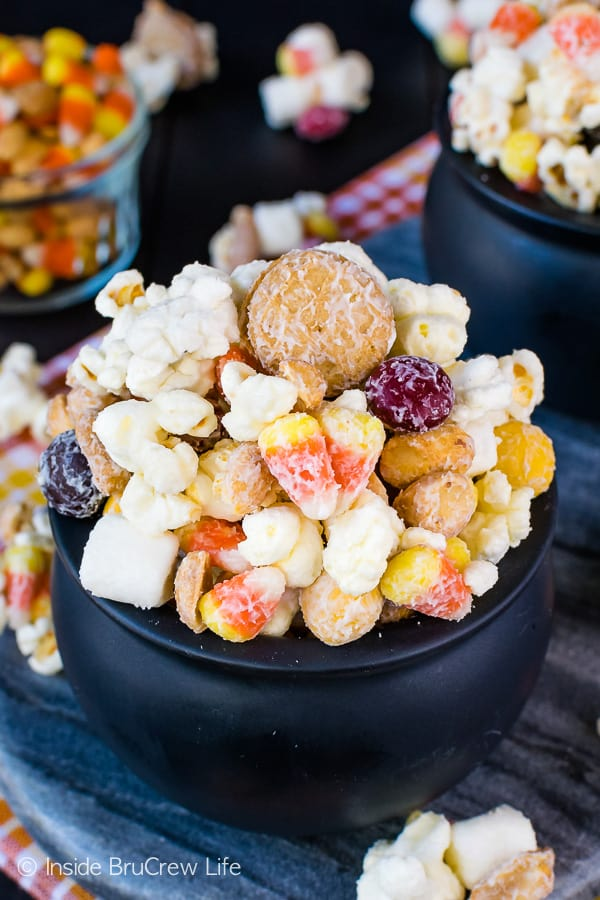 Candy Corn Popcorn Mix - white chocolate coated cookies, popcorn, and candy makes and awesome fall snack mix. Try this easy no bake recipe for Halloween parties! #snackmix #popcorn #whitechocolate #candycorn #peanuts #nutterbutters #fall #halloween #partymix