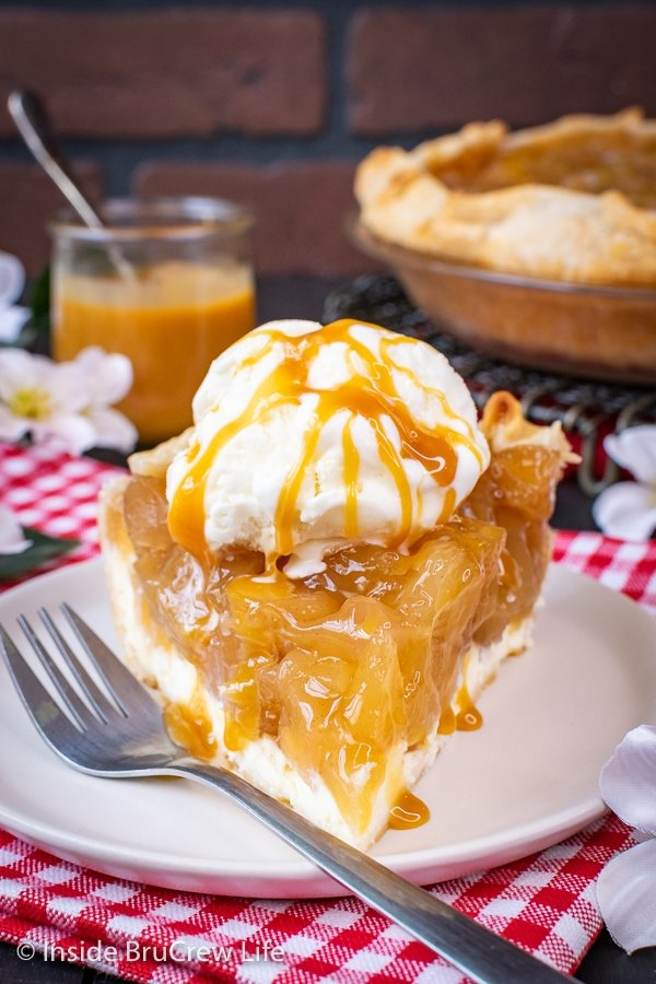 A slice of cheesecake apple pie with ice cream and caramel on a white plate with a fork