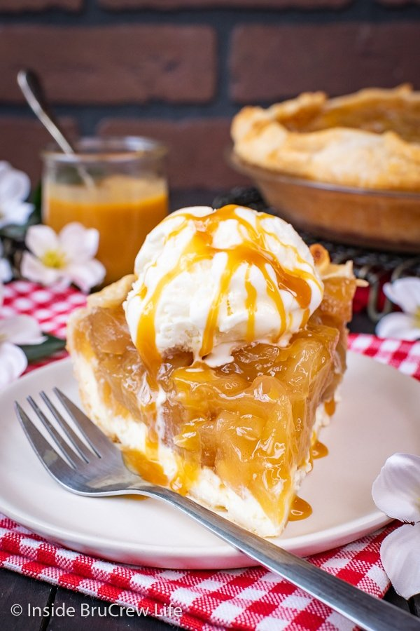 A slice of cheesecake apple pie topped with ice cream and caramel on a white plate with a fork