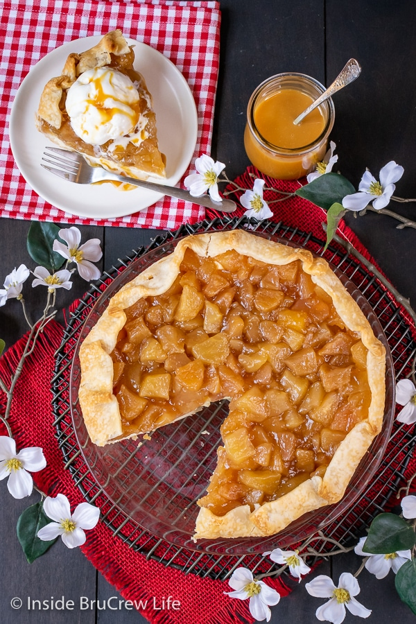 Overhead picture of an apple pie with a layer of cheesecake in it on a dark board