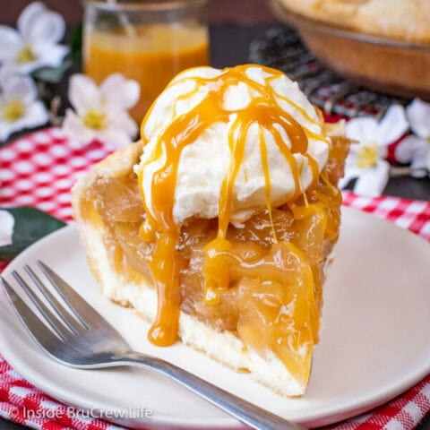 A white plate on a checkered towel with a slice of cheesecake apple pie with caramel drizzles and ice cream