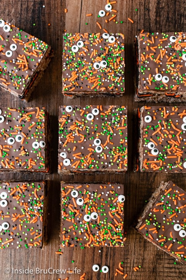 Rice krispie treats topped with chocolate, sprinkles, and candy eyes on a brown board.