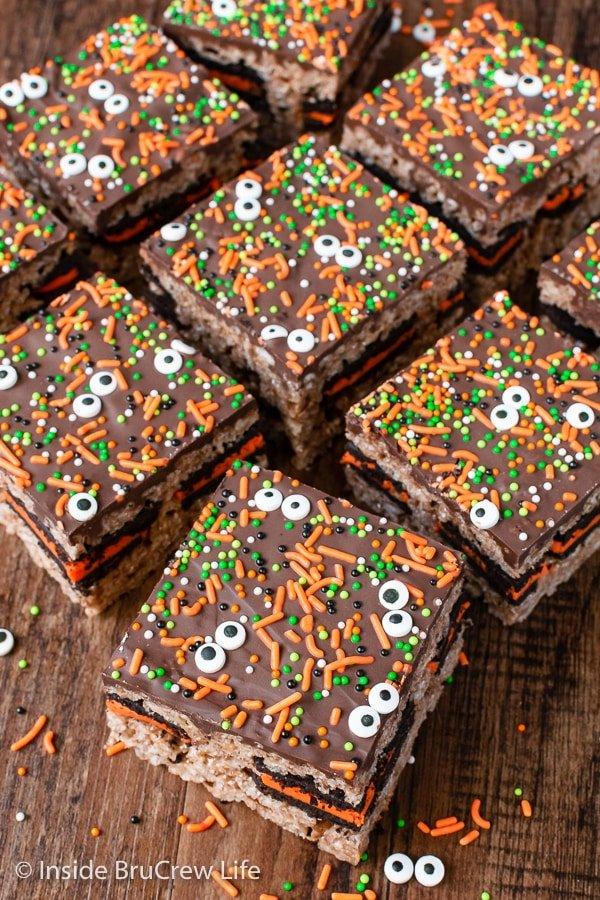A brown board with chocolate rice krispie treats topped with chocolate and sprinkles on it.