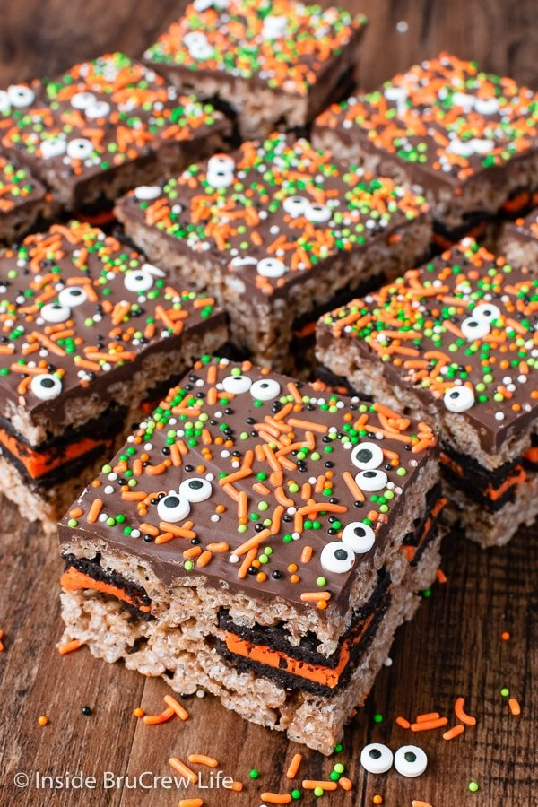 A brown board with squares of Oreo rice krispie treats topped with chocolate and sprinkles on it.