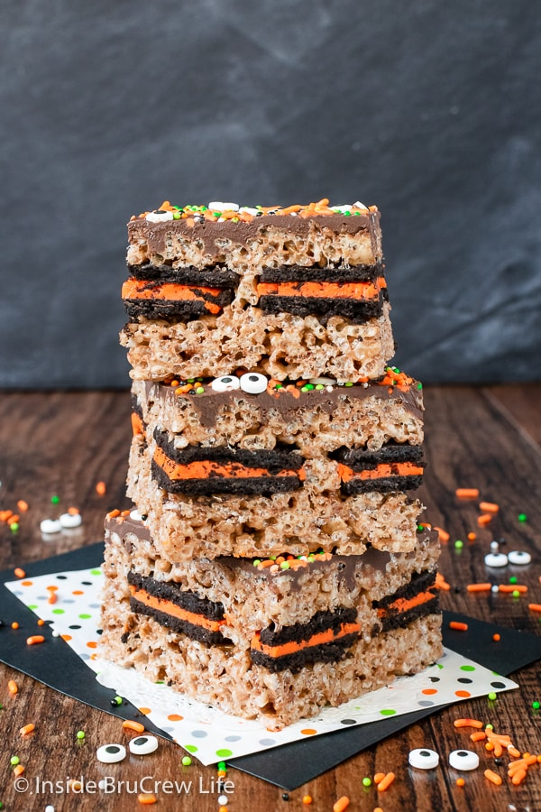 Three halloween rice krispie treats stacked on top of each other on a brown board.