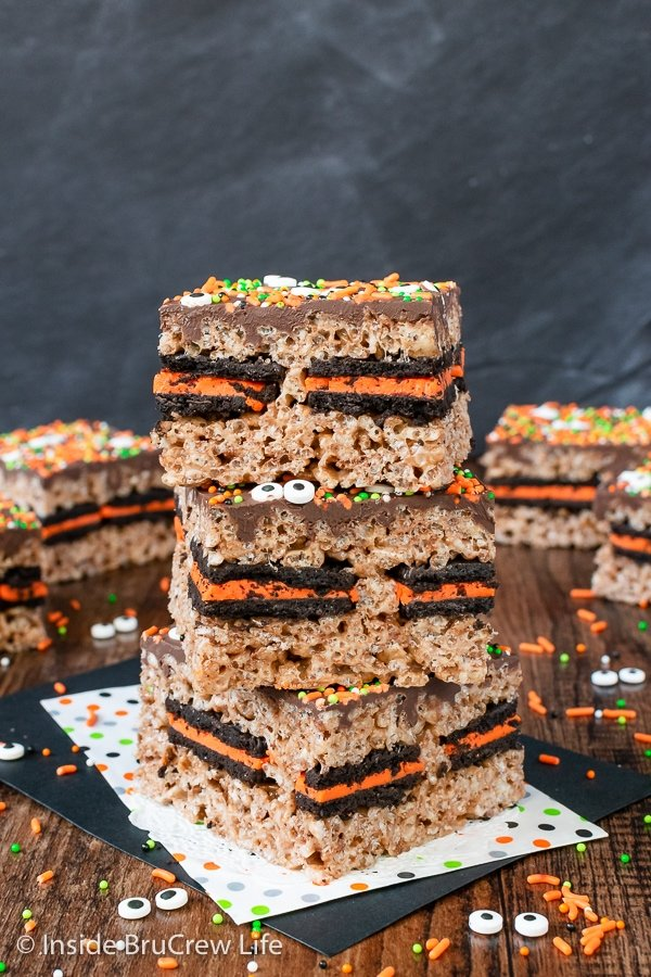 Three halloween rice krispie treats topped with chocolate and sprinkles stacked on top of each other.