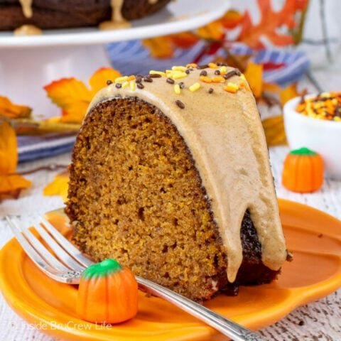 An orange plate with a slice of pumpkin bundt cake topped with maple glaze.