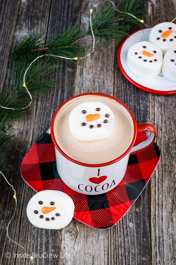 Floating Marshmallow Snowmen - use large marshmallows and melted chocolate to add snowmen faces to your hot chocolate. Easy edible craft for kids to make! #marshmallow #snowmen #hotchocolate #ediblecraft #easy #holiday