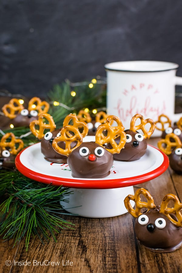 Peanut Butter Reindeer - pretzels and candy eyes add a fun reindeer look to these peanut butter balls. Easy recipe to make for holiday parties! #peanutbutter #truffles #chocolate #reindeer #christmas #nobake