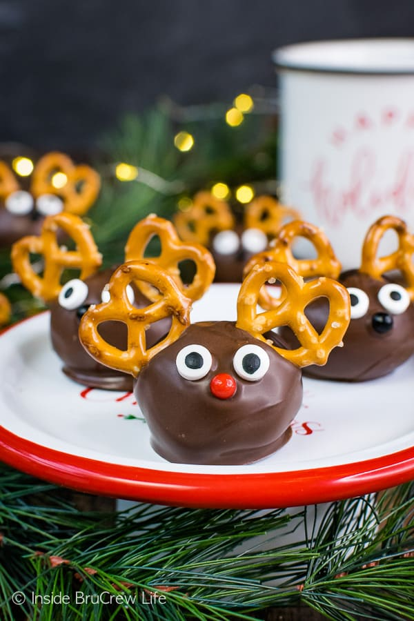 Peanut Butter Reindeer - candy eyes and pretzels turn these no bake peanut butter balls into a cute reindeer truffle. Easy recipe to make when you do not have time to bake. #peanutbutter #truffles #chocolate #reindeer #christmas #nobake
