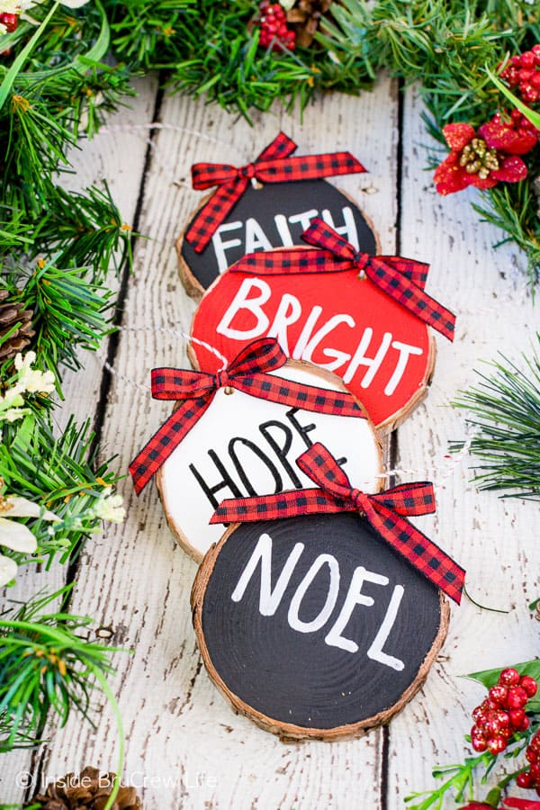 Rustic Wood Ornaments - wood ornaments painted with red, white, and black and holiday words. Easy wood craft to make and hang on your tree or garland. #rustic #woodornaments #raedunninspired #farmhousedecor #woodcrafts #christmastreeornaments