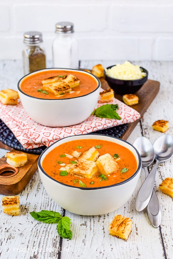 A white background with two white bowls filled with creamy tomato soup and grilled cheese cubes