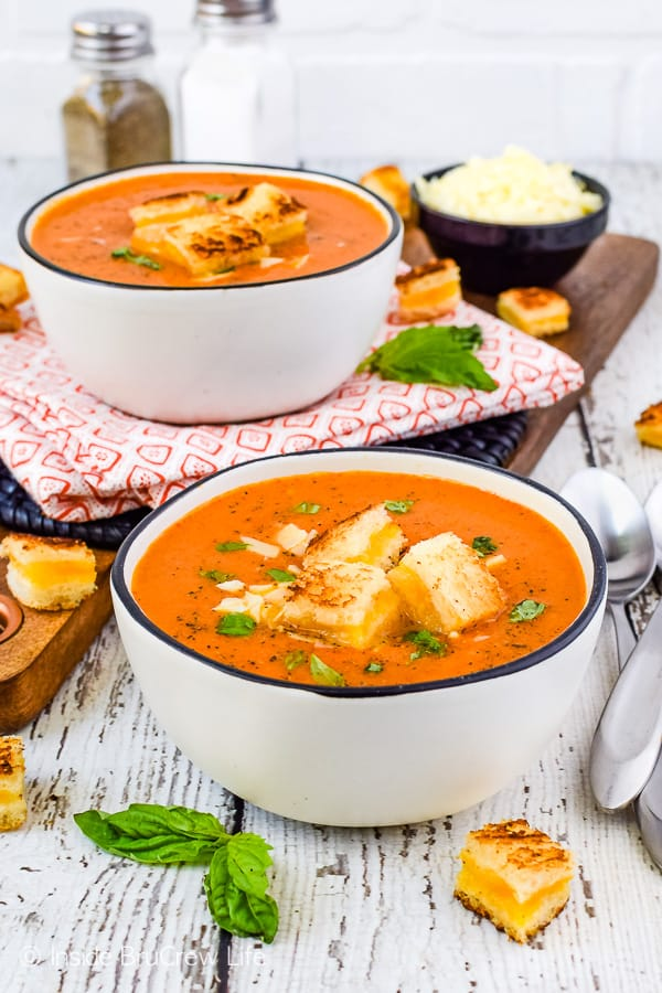 Two white bowls filled with homemade tomato soup and topped with grilled cheese sandwich bites