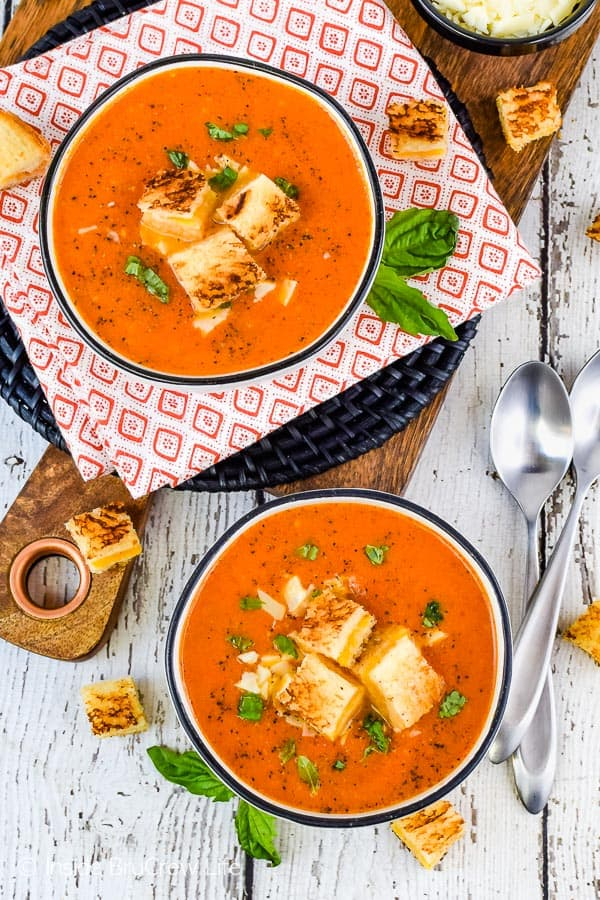 Overhead picture of two bowls filled with creamy tomato soup topped with grilled cheese cubes