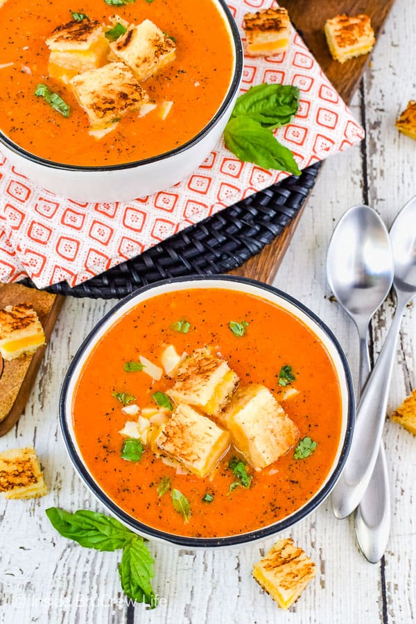 Overhead picture of two white bowls on a white board filled with homemade tomato soup