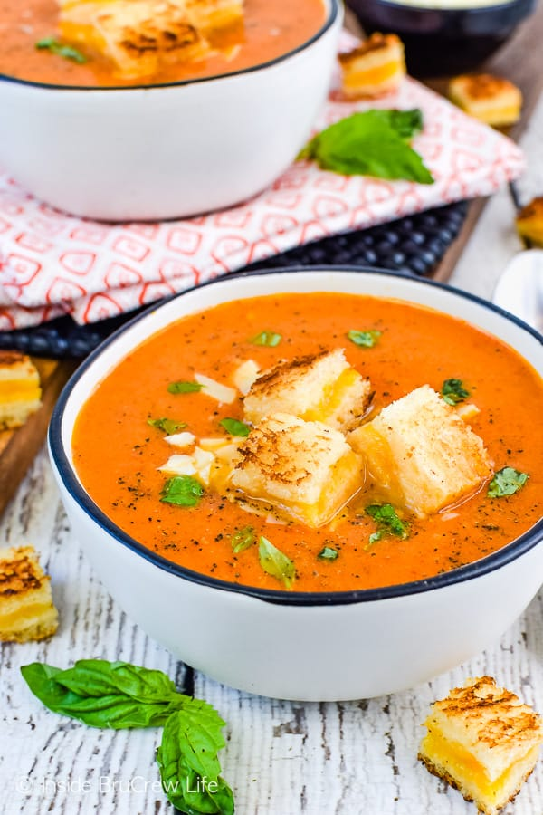 Close up picture of a white bowl filled with creamy tomato soup and topped with grilled cheese sandwich cubes