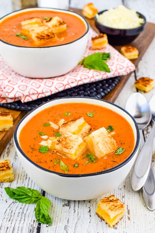 A white bowl filled with creamy tomato soup and topped with grilled cheese cubes