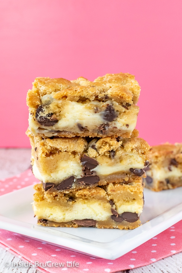 A stack of chocolate chip cheesecake bars on a white plate with more behind it.