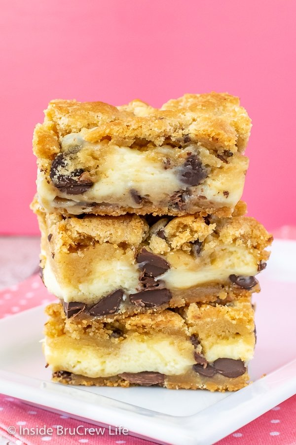 A stack of three chocolate chip cheesecake cookie bars on a white plate with a pink background.